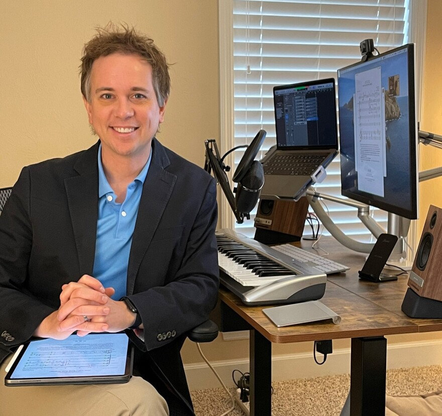 Michael Hanawalt poses at his home office with equipment he uses for Zoom rehearsals and classes.