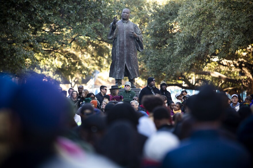 People gather around Martin Luther King Jr. statue on UT Austin campus.
