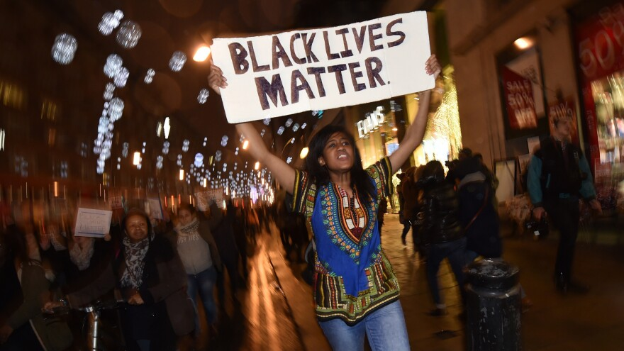 Demonstrators hold up signs Wednesday and march down Oxford Street, a shopping district in central London, as they protest a U.S. grand jury's decision not to indict the policeman who killed unarmed black teenager Michael Brown in Ferguson, Mo. More than 1,000 people demonstrated outside the U.S. embassy in London before moving onto Oxford Street.