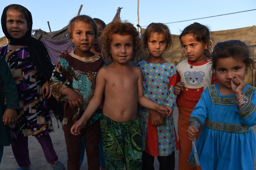 Afghan children look on at a refugee camp in Jalalabad on May 3, 2015. Like thousands of Afghan returnees, Neik Mohammad became unwanted in Pakistan after a Taliban massacre at a Peshawar school, forcing him to return home to a life of misery and fear in a squalid refugee settlement.