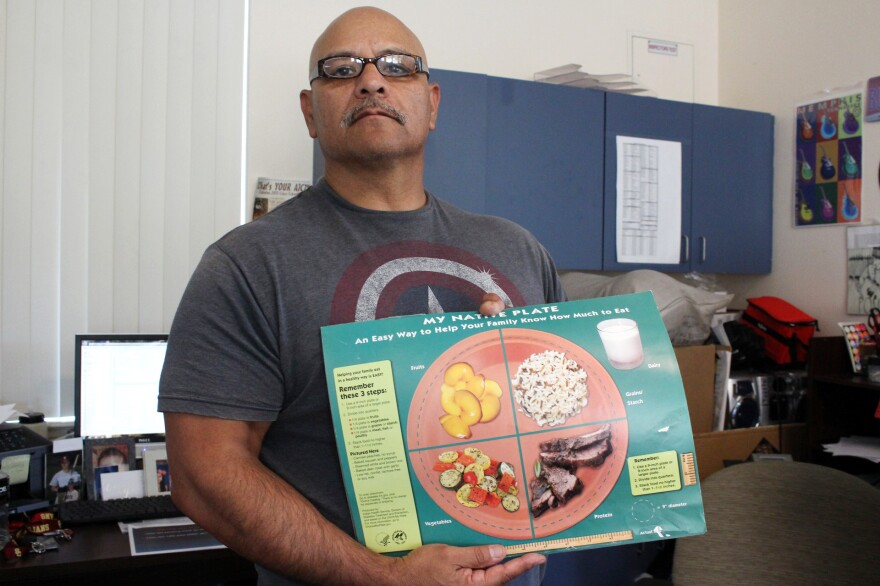 """Gonzales shows off a food guide for patients in the clinic's diabetes prevention program. He tells clients to stay away from processed foods and """"get off the couch."""""""