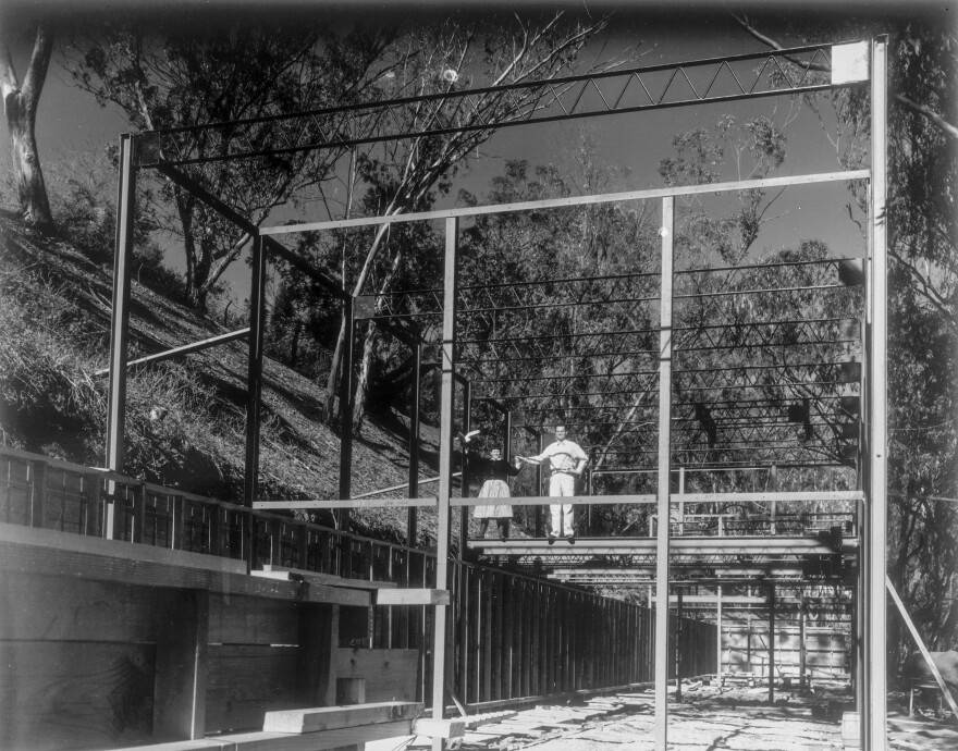 Ray and Charles Eames stand on the steel frame of their home-in-progress in 1949.