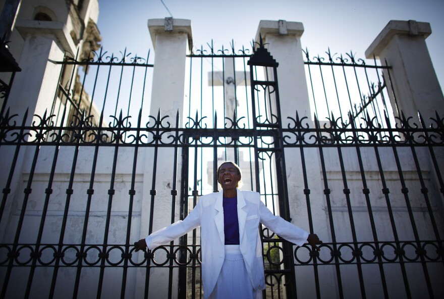 A woman cries in front of the gates of the destroyed cathedral in Port-au-Prince. The country's devastating earthquake on Jan. 12, 2010, destroyed hundreds of thousands of structures, including many government and public buildings.