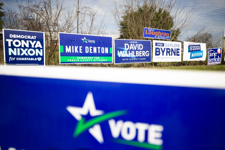 Signs for candidates running in local primary elections are posted at the corner of Manor Road and Airport Boulevard.