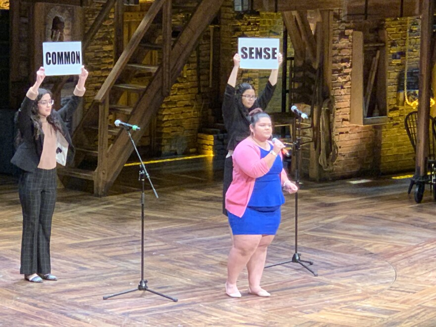 """Woman sings on stage while two classmates hold up signs that say """"Common Sense."""""""