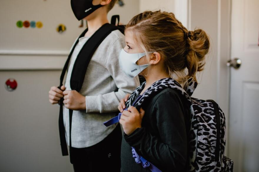 A boy and girl wearing masks and backpacks prepare to leave for school.