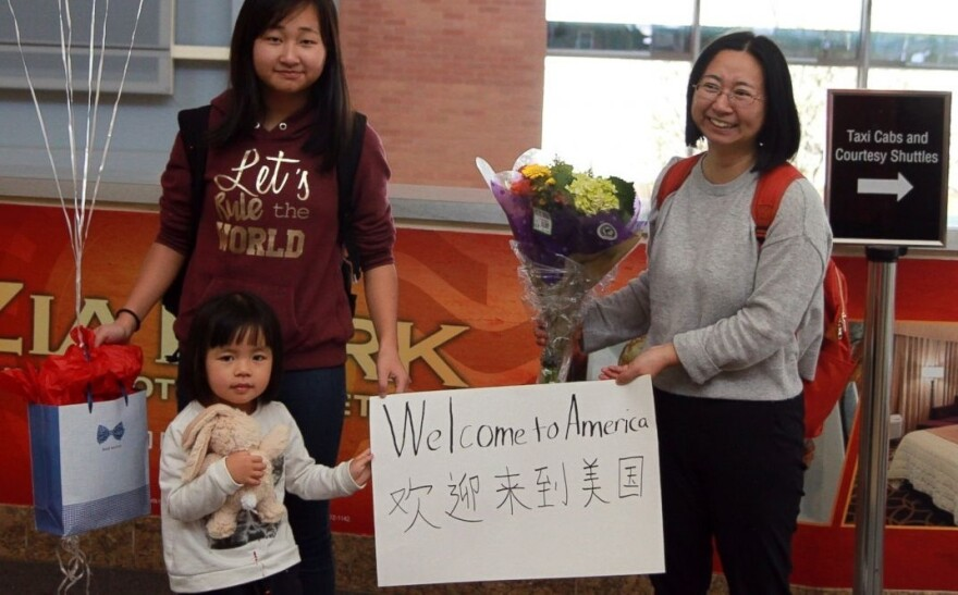 In this photo from March 17, released by China Aid, Chen Guiqiu (right) holds a welcome sign with her daughters Xie Yajuan, 15, and Xie Yuchen, 4, after arriving at an airport in Texas. Chen's husband, lawyer Xie Yang, was charged with inciting subversion.