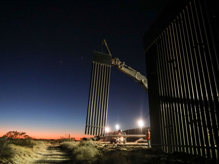 Workers construct wall in the desert between Sundlad Park, N.M., and Ciudad Juarez, Mexico, last month.