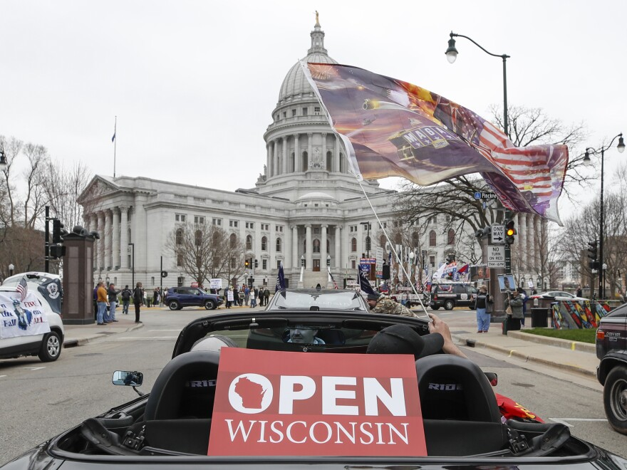 People in cars participate in a protest against the coronavirus shutdown last month in front of the state Capitol in Madison, Wis.
