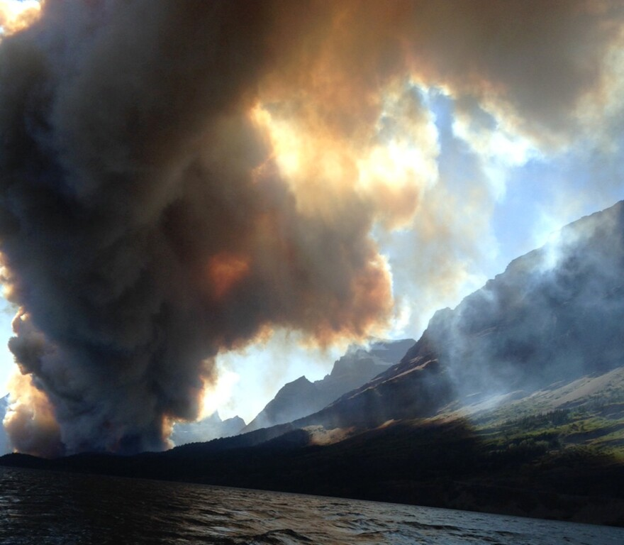Smoke from the the Reynolds Creek wildfire rises above the landscape at St. Mary Lake in Glacier National Park, Mont.