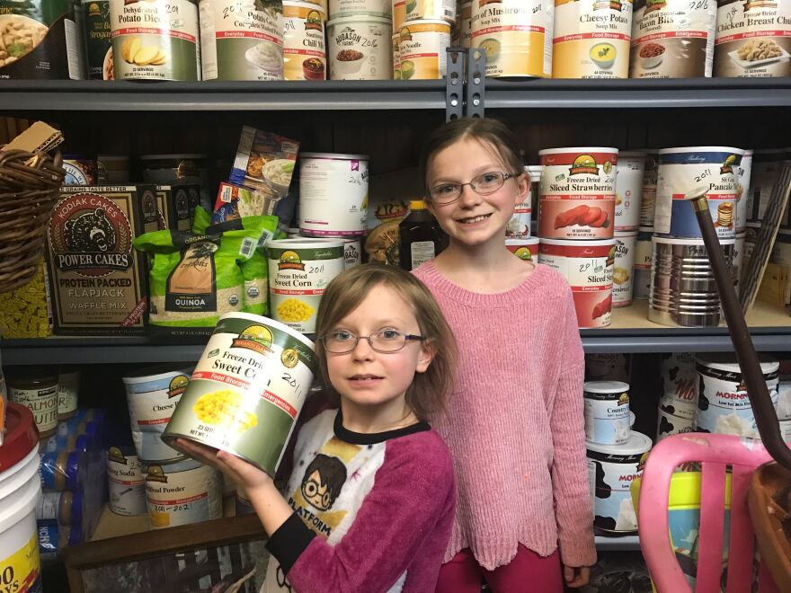 Phot of young girls in front of shelves of canned goods.