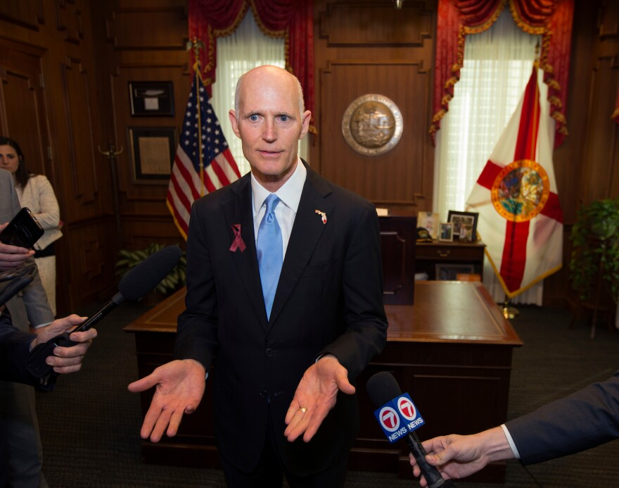 This March 9, 2018 file photo shows Florida Gov. Rick Scott talking to the media at the Florida Capital in Tallahassee, Fla. Attorney General Pam Bondi on Wednesday, April 4, 2018, appealed Judge Mark Walker's ruling to U.S. Court of Appeals.