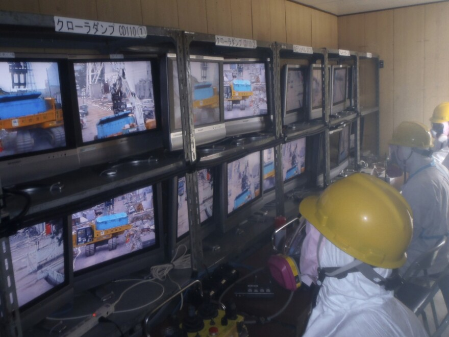 Workers operate remote-controlled rubble-removing equipment at the Fukushima Dai-ichi nuclear complex. Though robotic machines will be able to clear some of the larger debris from the facility, some people will most likely be needed to work inside the reactor buildings.