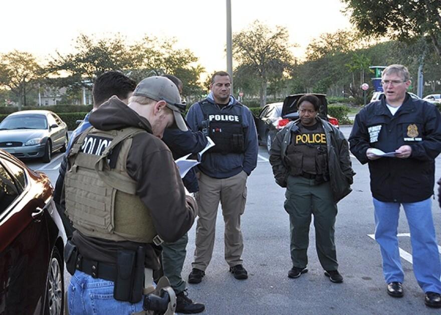 Law enforcement officials gather in a parking lot