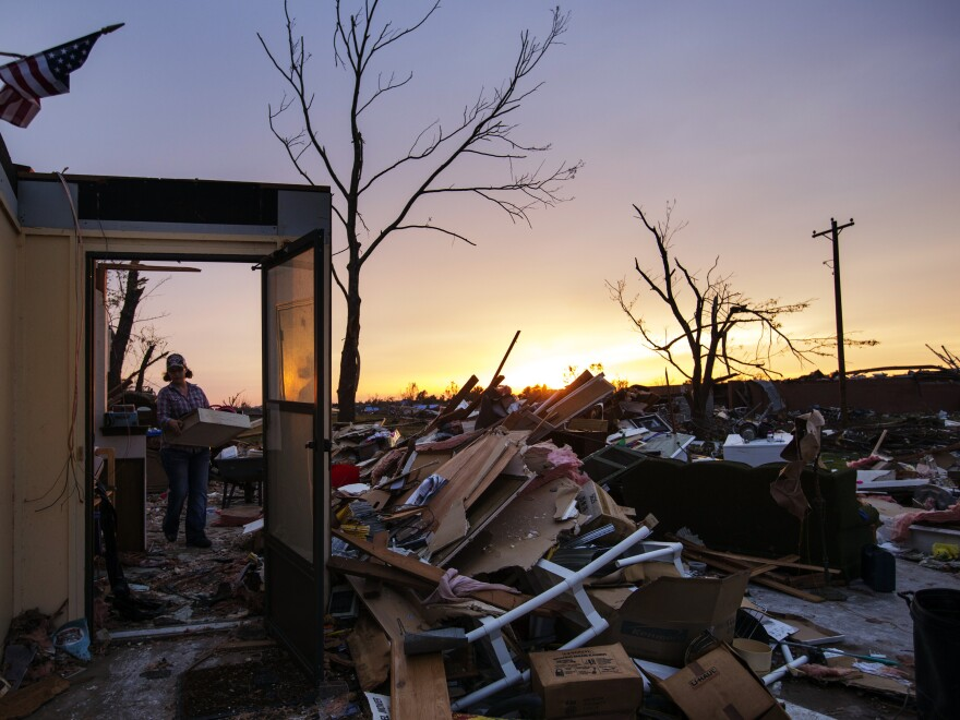 Rita Green carried a plastic bin of items as she helped a family friend salvage things from a home Thursday in Moore, Okla.