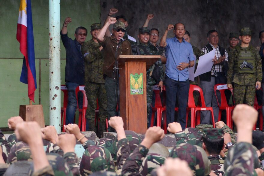 """Philippine President Rodrigo Duterte (on stage in brown) raises a clenched fist as he declares Marawi """"liberated"""" during a ceremony in the Bangolo district of Marawi on Tuesday."""