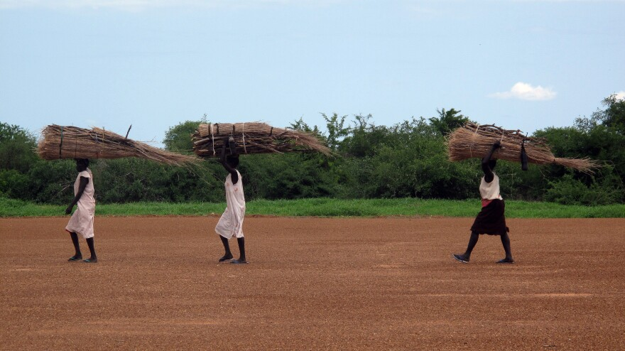 Women carry sticks in Ganyliel, South Sudan, an area protected from the violence in the country due to its isolation. But food there is scarce.