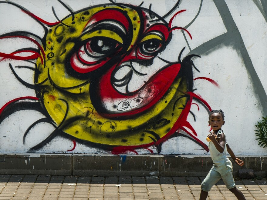 """A child walks past a COVID-19 graffiti in Soweto's Orlando West township near Johannesburg, South Africa, on Thursday. Africa has surpassed 2 million confirmed coronavirus cases as the continent's top public health official warns that """"we are inevitably edging toward a second wave"""" of infections."""