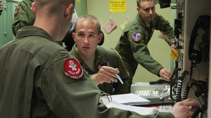 First Lt. Patrick Romanofski (center) and 2nd Lt. Andrew Beckner (left) practice the launch of nuclear weapons. Promotions are now more strongly influenced by hands-on performance in this simulator.