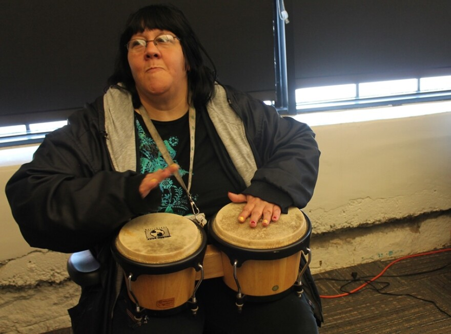 Rita Schneider, playing bongos at the Independence Center, is exhibiting in the Gallery 201 show.