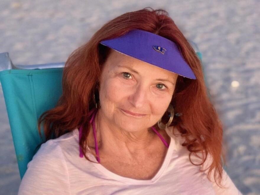 A woman wearing a purple sun visor sitting on a beach chair.