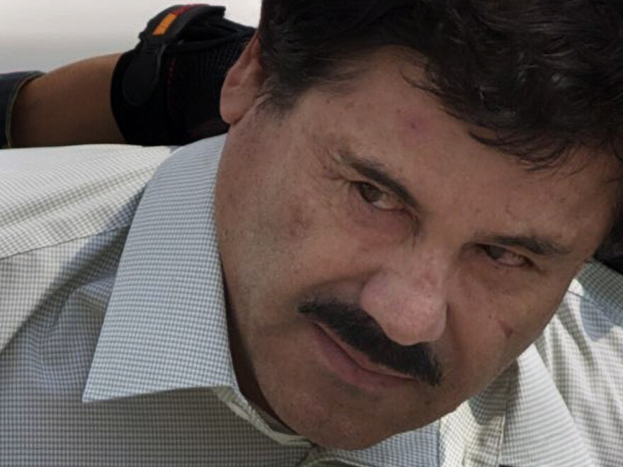 """Joaquin """"El Chapo"""" Guzman is escorted to a helicopter in handcuffs by Mexican navy marines at a navy hangar in Mexico City after his capture last year. Guzman escaped from a maximum security prison for the second time this July; today, Mexican authorities announced he evaded an attempt to recapture him."""