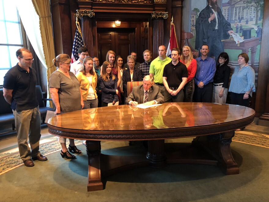 Missouri Gov. Mike Parson is joined by members of his staff Friday as he signs budget bills.