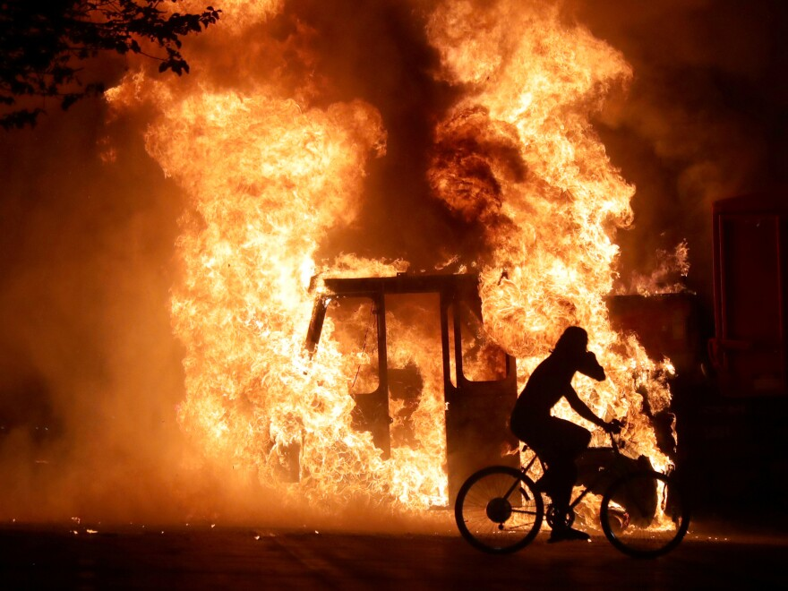 A man on a bike rides past a city truck on fire outside the Kenosha County Courthouse in Kenosha, Wis., during protests following the police shooting of Jacob Blake, a Black man, on Sunday.