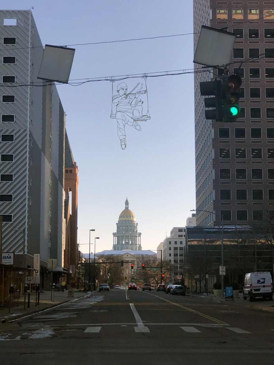 A wire sculpture of Elijah McClain playing violin to a cat hangs high above a street, the state Capitol dome visible in the background.