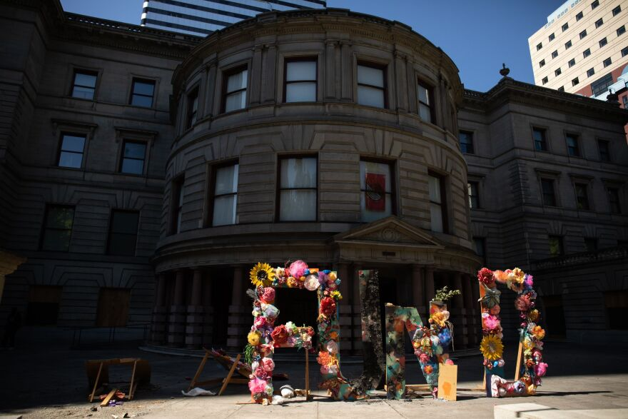 """A man knocked out the """"DE"""" in """"DEFUND"""" outside Portland City Hall on Aug. 30, 2020."""