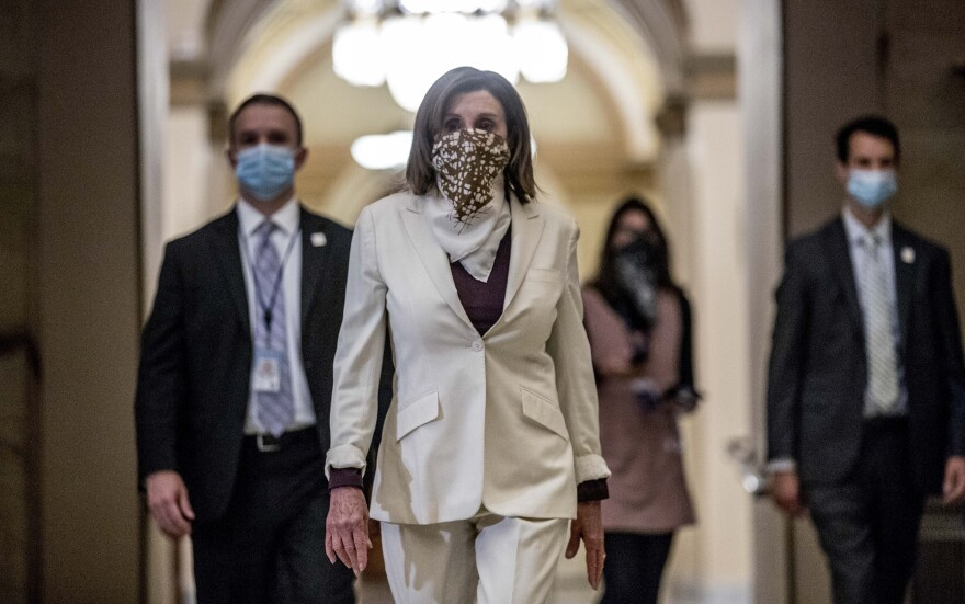 House Speaker Nancy Pelosi, wearing a face covering, walks to her office on Capitol Hill Thursday after signing the latest coronavirus relief package.