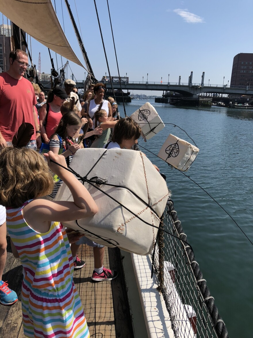 Tourists reenact the Boston Tea Party by tossing tea over the side of the ship into the Boston Harbor.