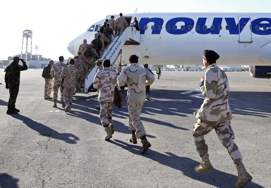 A batch of former rebels who have joined the Libyan army board a plane in Tripoli on Jan. 9. They were headed to Italy to receive training.