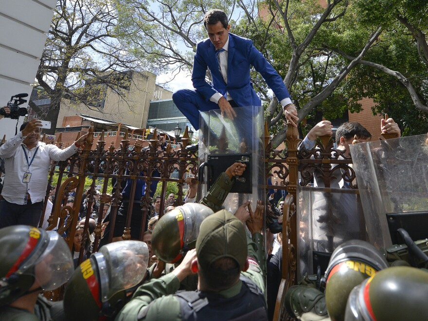 National Assembly President Juan Guaidó climbs the fence in a failed attempt to enter the compound of the legislature, as he and other opposition lawmakers are blocked from entering a session to elect new assembly leadership in Caracas, Venezuela, on Jan. 5.