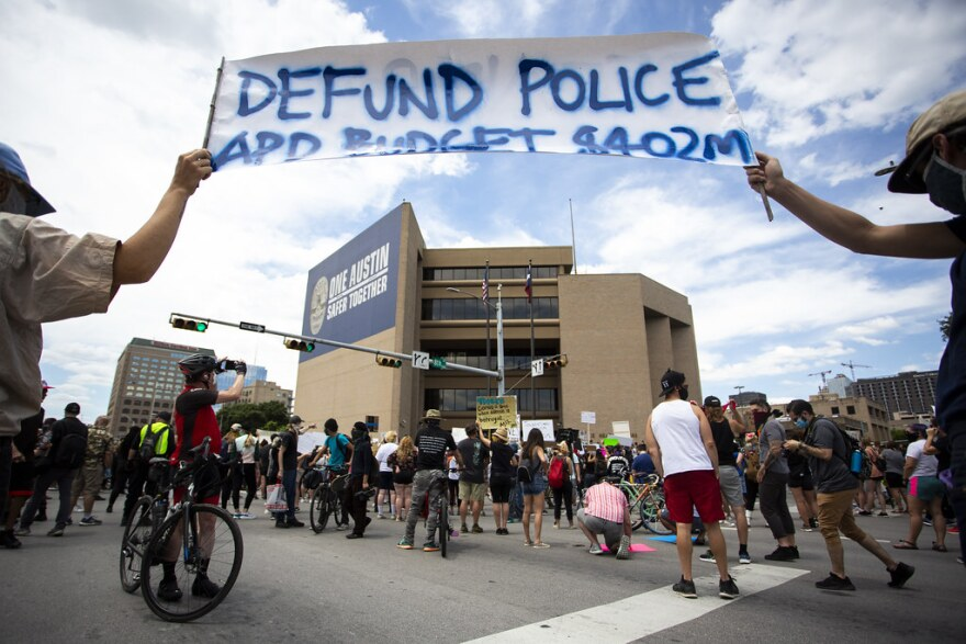 """Protesters hold a sign saying """"Defund Police"""" in front of Austin Police headquarters in May."""