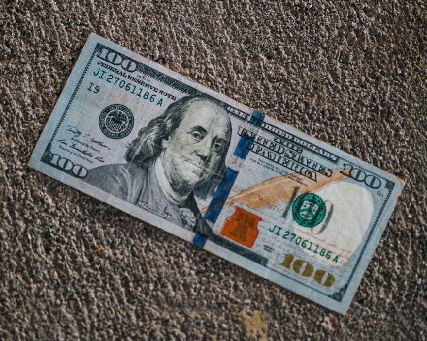 A 100-dollar bill laying on concrete.
