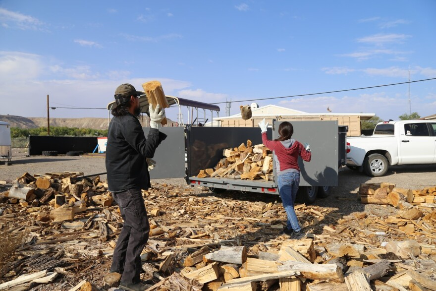 A man and woman load wood into a truck