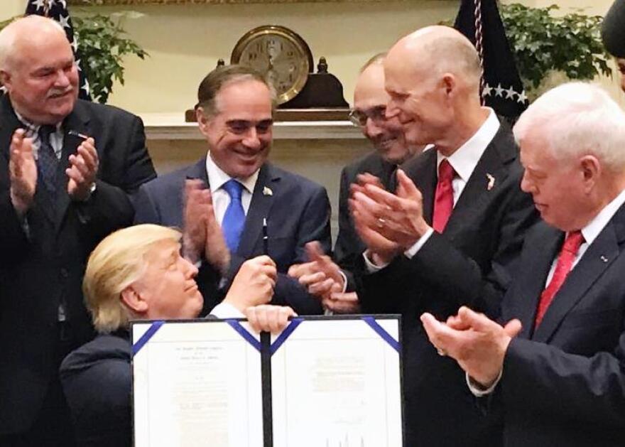 President Trump passes out pens after signing the Veterans Choice Program Extension and Improvement Act. From right to left: Florida VA Ex. Dir. Glenn Sutphin, Florida Gov. Rick Scott, Chairman U.S. House VA Committee Phil Roe, VA Secretary David Shulkin.