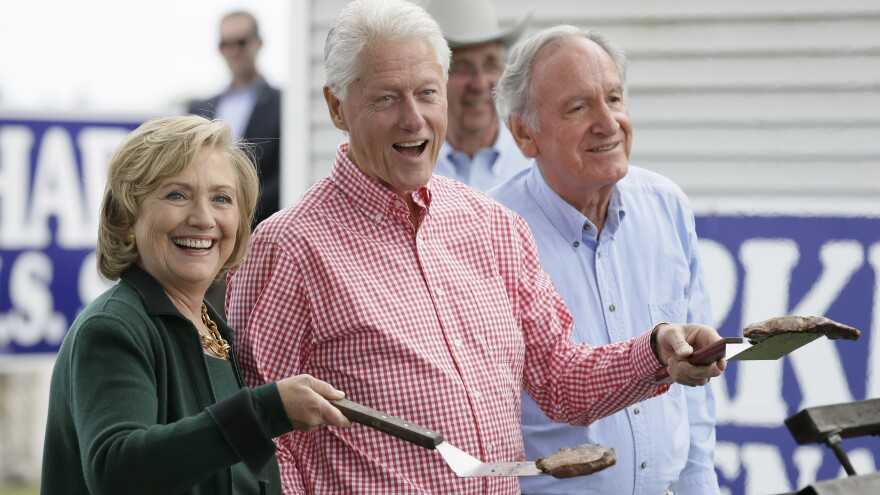 Former Secretary of State Hillary Clinton, former President Bill Clinton and U.S. Sen. Tom Harkin work the grill during Harkin's annual fundraising steak fry in Indianola, Iowa, on Sunday.
