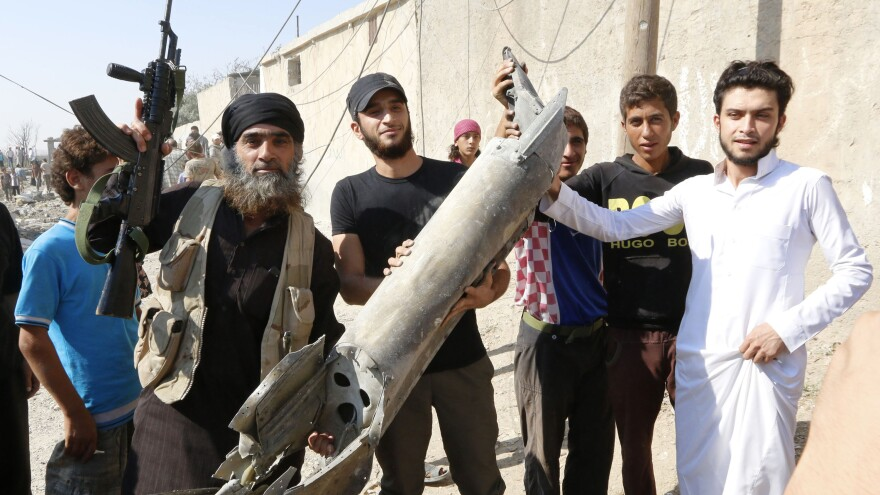 An Islamic State militant, left, stands next to Raqqah residents Sept. 16 as they hold pieces of wreckage from a Syrian war plane after it crashed in the northeast Syrian town.
