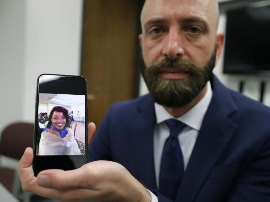 Eric Ridenhour poses with a photo he took of his fiance, Kiersten Smith. Smith was killed June 9 when a crane collapsed onto their apartment.