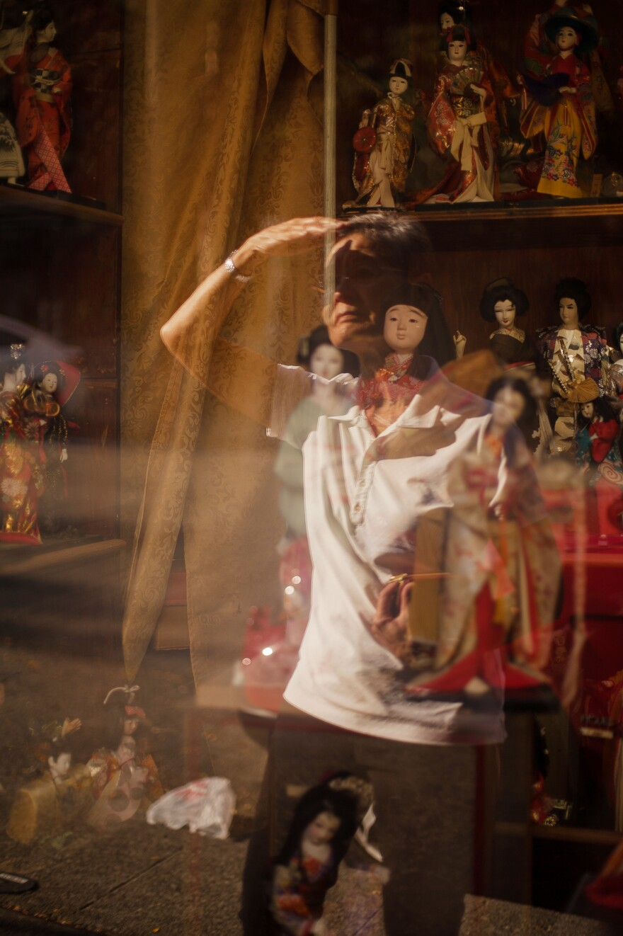 Sharon Sakamoto looks at a display of <em>Hinamatsuri</em>, or Girls' Day, dolls at Seattle's Chinatown-International District. Sakamoto has memories of her mother displaying traditional ornamental dolls to celebrate Girls' Day and Boys' Day.