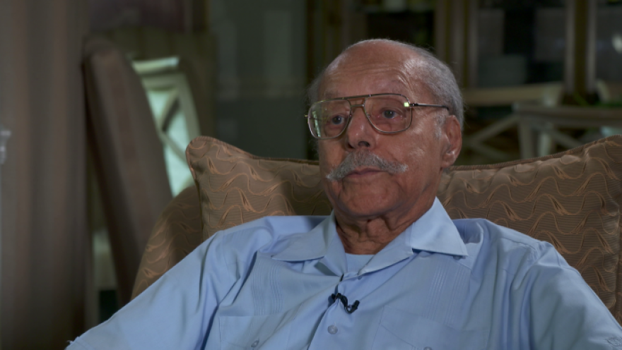 An elderly man relaxes in a tan colored chair as he speaks to a camera.