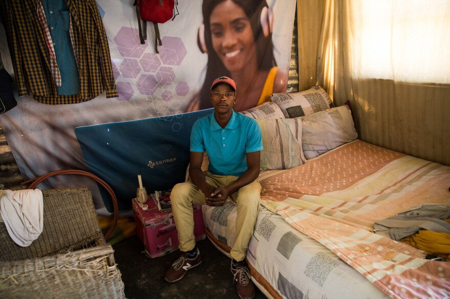 """As people settle into their shacks in Covid, they start to unpack small comforts that make a place feel like home. Sivuyile Duma put up photos of his brothers and friends. """"If I'm going to be here permanently I want to make it feel like home,"""" said Duma."""