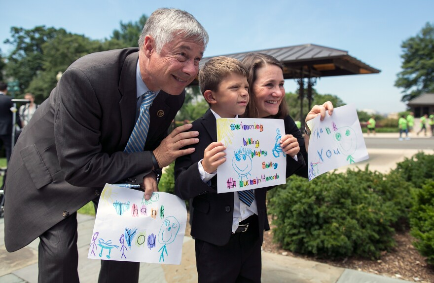 Rep. Fred Upton, a Michigan Republican, (left) and Rep. Diana DeGette, D-Colo., hold thank you signs made by Max Schill, 6, from Williamstown, N.J., after the House of Representatives voted in favor of the 21st Century Cures Act in 2015.
