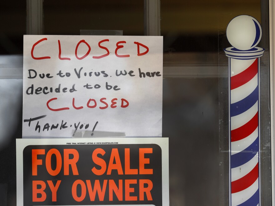 """For Sale By Owner"" and ""Closed Due to Virus"" signs are displayed in a storefront in Grosse Pointe Woods, Mich. on April 2, 2020. The coronavirus has triggered a stunning collapse in the U.S. workforce."