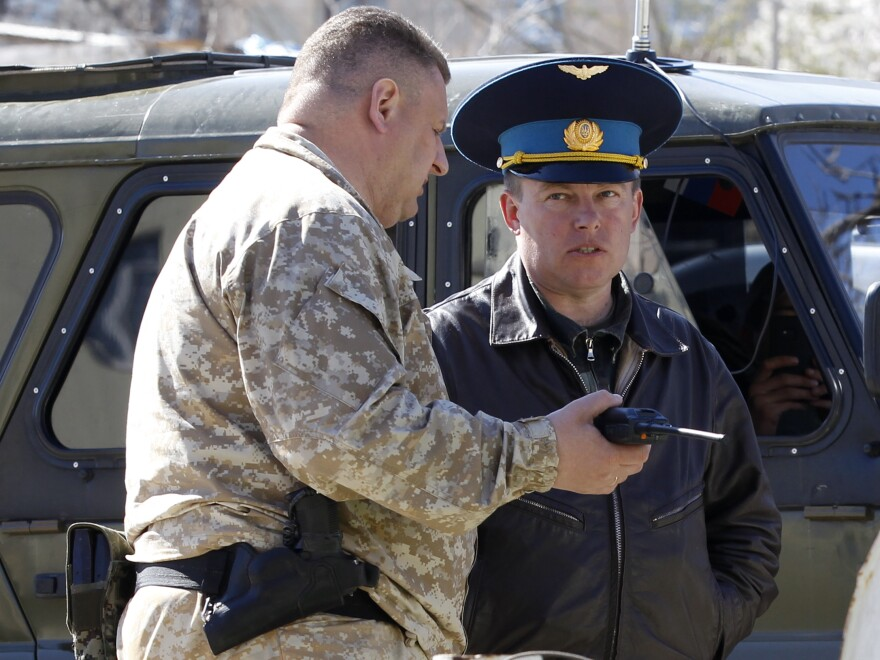 A Russian military officer, left, talks to Ukrainian Col. Yuli Mamchur before the Russian takeover of an air base near the Crimean town of Belbek on Saturday.