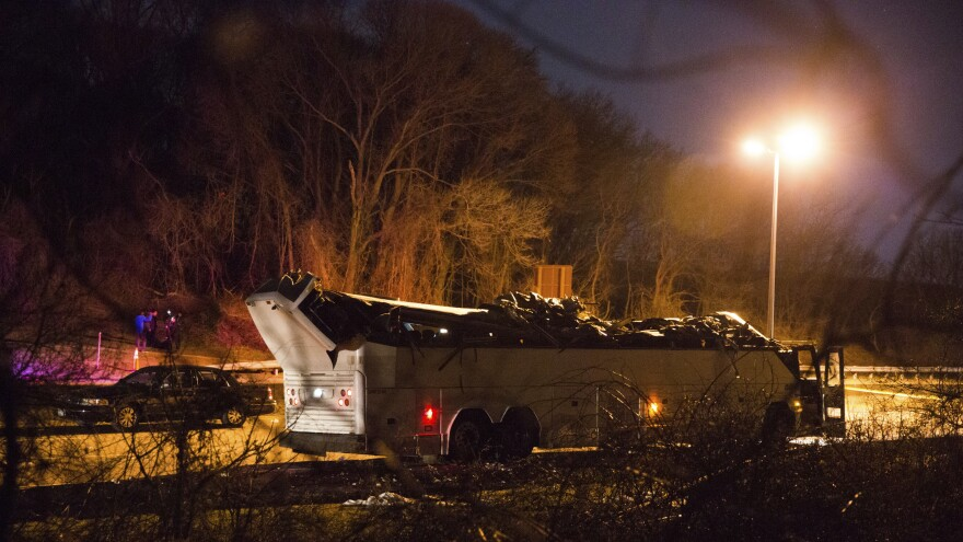 A bus that was carrying teenage passengers sits on the side of the roadway after it hit an overpass on the Southern State Parkway in Lakeview, N.Y., on Sunday.