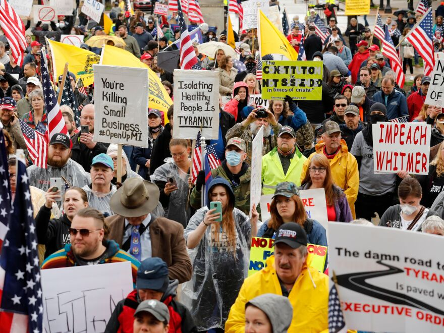 Demonstrators take part in a rally organized Thursday by Michigan United for Liberty on the steps of the Michigan State Capitol in Lansing, demanding the reopening of businesses.