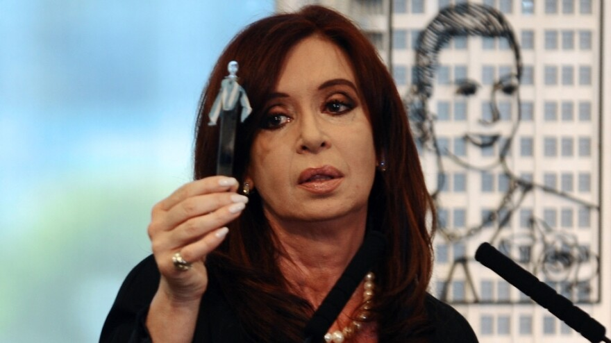 Argentine President Cristina Fernandez holds a petroleum sample as she announces plans for her government to nationalize a giant oil company that is largely owned by a private Spanish company, Repsol. Behind her is an image of the country's former first lady, Eva Peron.